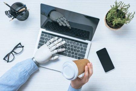 Foto de Vista parcial del empresario con brazo prostético tomando café de la taza de papel y el uso de laptop en mesa de oficina - Imagen libre de derechos