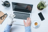 cropped image of businessman with prosthetic arm using laptop at table with potted plant and cup of coffee