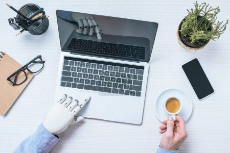 cropped image of businessman with prosthetic arm using laptop and holding coffee cup at table