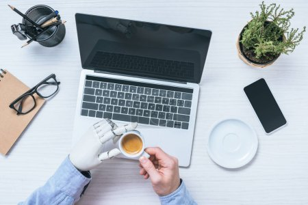 Photo for Partial view of businessman with prosthetic arm drinking coffee at table with laptop in office - Royalty Free Image