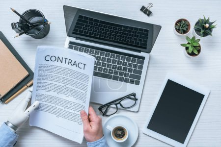 cropped image of businessman with prosthetic arm reading contract at table in office