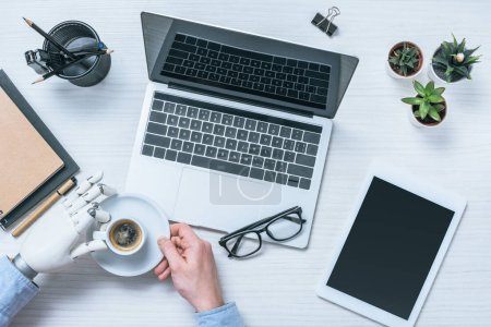 cropped image of businessman with prosthetic arm drinking coffee at table with laptop, digital tablet and eyeglasses