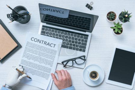 cropped image of businessman with prosthetic arm signing contract at table