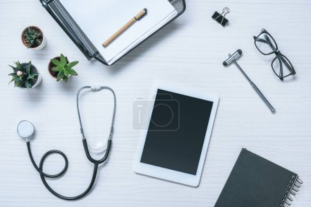 elevated view of doctor workplace with textbook, stethoscope, reflex hammer and digital tablet on table