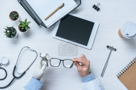 Photo for Cropped image of male doctor with prosthetic arm holding eyeglasses at table with blank digital tablet - Royalty Free Image