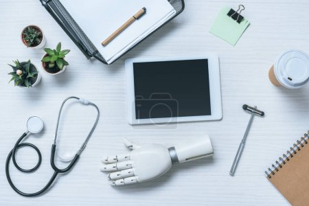 Photo for Top view of doctor workplace with prosthetic arm, stethoscope, reflex hammer and digital tablet with blank screen on table - Royalty Free Image