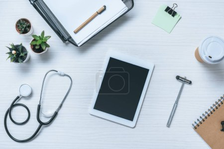 top view of digital tablet with blank screen, stethoscope, reflex hammer and paper cup of coffee on doctor table