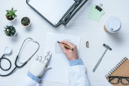 cropped image of male doctor with prosthetic arm writing on blank paper at table with reflex hammer, stethoscope and coffee cup