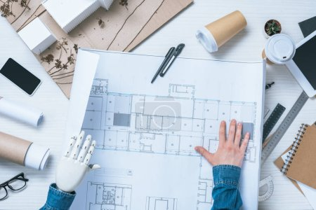 Photo for Partial view of male architect with prosthetic arm looking at blueprint - Royalty Free Image