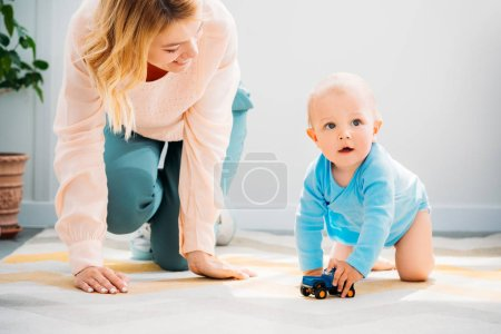 mother and child crawling together on carpet at home
