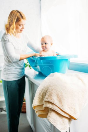 young mother bathing child in plastic bathtub at home