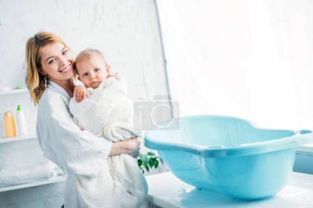smiling mother in bathrobe carrying adorable child covered in towel near plastic baby bathtub