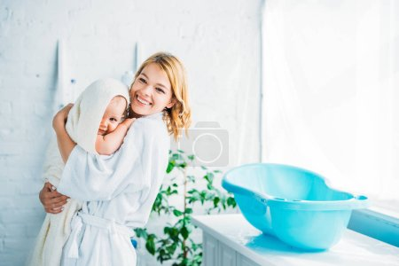 Photo for Happy mother in bathrobe carrying adorable child covered in towel near plastic baby bathtub - Royalty Free Image