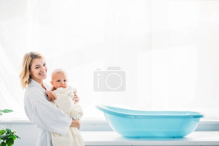 side view of happy mother in bathrobe carrying adorable child covered in towel near plastic baby bathtub