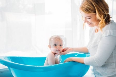 side view of happy mother washing her adorable little child in plastic baby bathtub at home