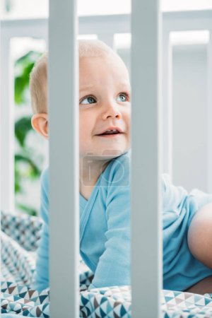 Photo for Adorable little baby lying in crib and looking away - Royalty Free Image