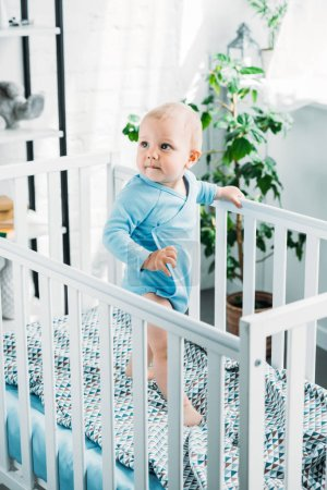 adorable little baby standing in crib and looking away