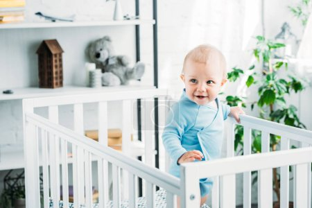 happy little baby standing in crib at home