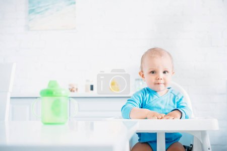 cute little baby sitting on high chair at kitchen and looking at camera