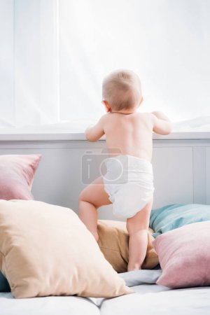 happy little baby standing on bed with lot of pillows and looking through window