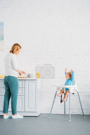 mother preparing dinner for her excited  little child while he sitting in feeding chair at kitchen