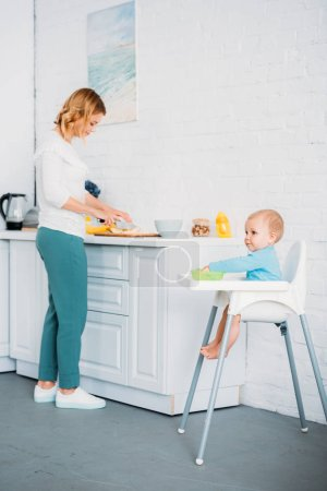 mother preparing dinner for her little child while he sitting in feeding chair at kitchen