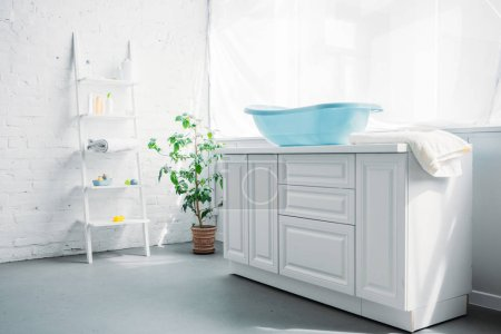 blue plastic childrens bathtub on stand in white modern room