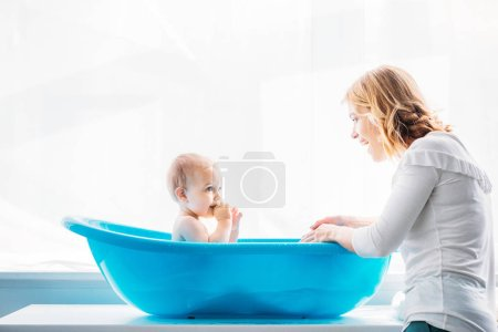 side view of smiling mother washing her adorable little child in plastic baby bathtub at home