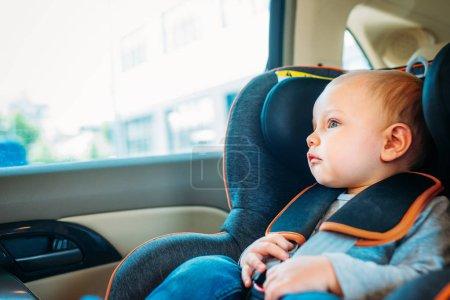 Photo pour Adorable petit bébé assis dans le siège auto en voiture et en regardant par la fenêtre - image libre de droit