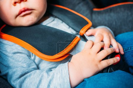 cropped shot of little baby sitting in child safety seat in car