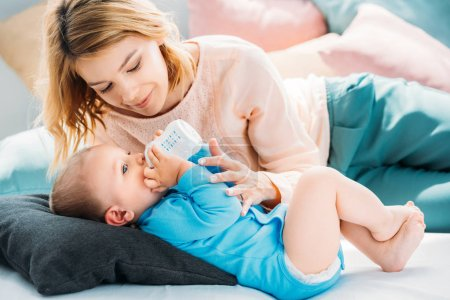 mother feeding her little child with baby bottle on bed at home