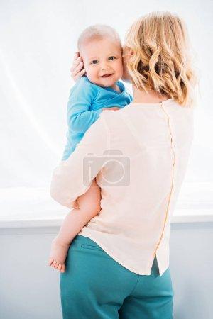 Photo pour Vue arrière de la mère portant son enfant heureux - image libre de droit