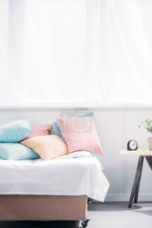 bed with lot of pillows in modern light room with alarm clock and plant of bedside table