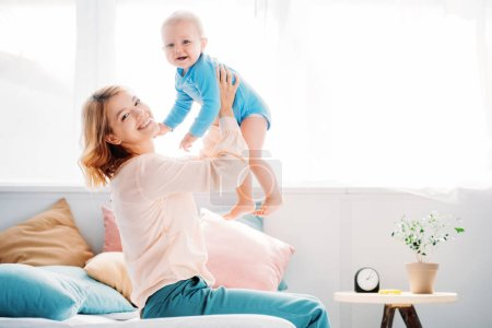 side view of smiling mother raising laughing little child while sitting on bed at home