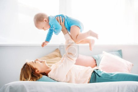side view of mother raising laughing little child while lying on bed at home