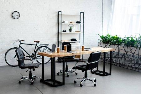 Photo pour Intérieur de bureau moderne avec les ordinateurs portables et les gobelets en papier sur la table - image libre de droit