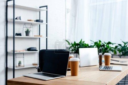 Photo pour Ordinateurs portables et les gobelets en papier sur la table dans le bureau moderne - image libre de droit