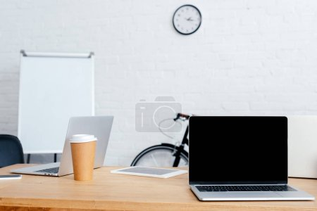 laptops, digital tablet and coffee to go on table in office