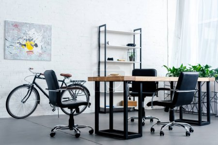 modern office interior with bicycle, table and chairs
