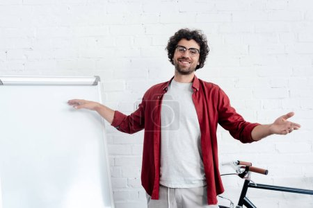 happy young man in eyeglasses pointing at whiteboard and smiling at camera