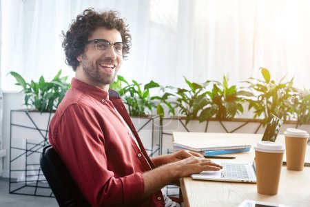 handsome young man in eyeglasses using laptop and smiling at camera in office