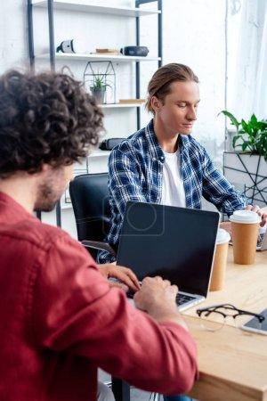 Foto de Recortada a tiro de sus colegas hombres trabajando con ordenadores portátiles en la oficina - Imagen libre de derechos