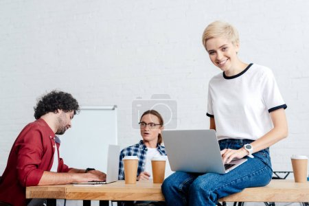 young woman using laptop and smiling at camera while male colleagues working behind