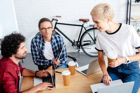 Foto de Jóvenes en marcha equipo utilizando ordenadores portátiles y bebiendo café de las tazas de papel en lugar de trabajo - Imagen libre de derechos