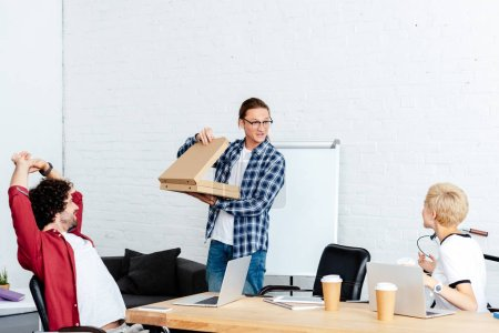 man holding pizza boxes and looking at colleagues at workplace