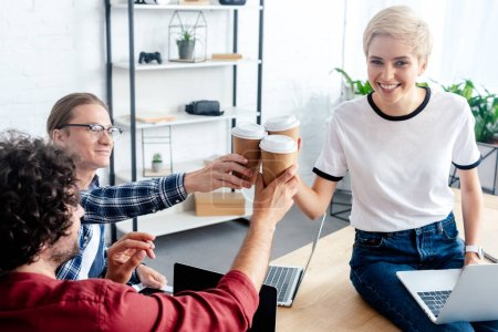 smiling young colleagues clinking paper cups while using laptops in office
