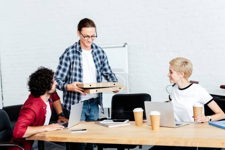 smiling young man holding pizza boxes while colleagues sitting at table in office