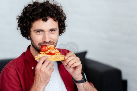 handsome young man eating pizza and looking at camera