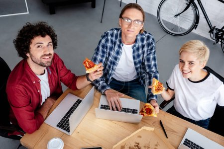 high angle view of smiling young start up team using laptops and eating pizza in office