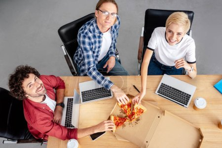 high angle view of happy young colleagues eating pizza and smiling at camera at workplace